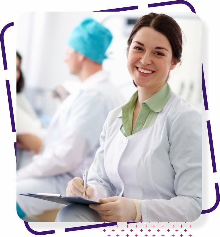 Uma dentista olhando para frente e sorrindo.