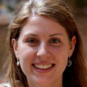 Foto de uma mulher já adulta, branca de cabelo longos e loiros sorrindo.
